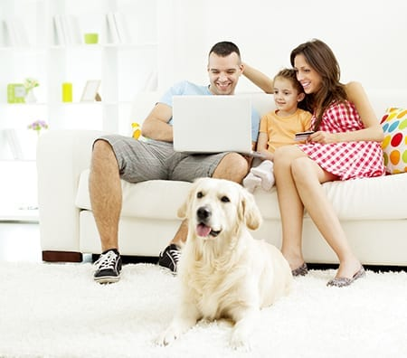 family sitting on couch looking at laptop with dog laying on floor