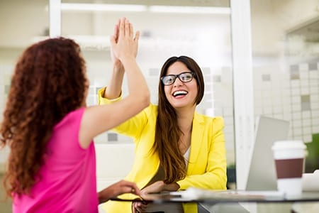 Two designers businesswomen giving high five to each other in office